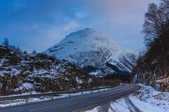 Winterstraßen-Abflussrinnenschnee caped Berge in Ost-Norwegen lizenzfreie stockbilder