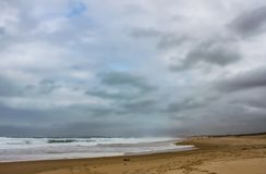 Winterstrand mit einem Sturm, der heraus zu den meeres- zwei Leuten braut, gehen in Abstand mit einem Hund und die Wellen stoßen  stockbilder