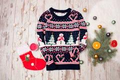Winterstrickjacke mit Weihnachtsmuster auf einem hölzernen Hintergrund, Tannenzweig mit Verzierungen und Zitrusfrucht Lizenzfreie Stockbilder
