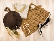 Winterstrickjacke und -Lederrock mit Zubehör vereinbarten auf dem Boden Stockfoto