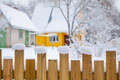 Winterszene in der Landschaft Bretterzaun im Schnee und Holzhaus am Hintergrund Schließen Sie oben mit bokeh Stockfotografie