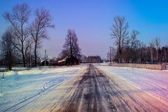 Wintertag im Dorf Bloße Bäume und Fahrbahnschnee Stockfotos