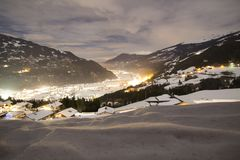 Wintertal in den Alpen iluminated durch die Stadtlichter lizenzfreies stockbild
