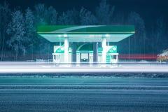 WinterTankstelle nachts mit langen hellen Bahnen von den Scheinwerfern des Führens von Autos Stockbild