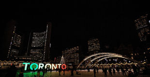 Wintertime Festivities in Toronto, Canada. Ice skating against the backdrop of the Toronto skyline in downtown Toronto, Ontario, in Nathan Phillips Square NPS Royalty Free Stock Photos