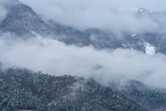 Fog revealing the mountain range royalty free stock photo