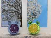 Wintertime versus springtime. 3D render of two alarm clocks indicating wintertime and springtime placed on windowsill with two pane-window showing outdoor Stock Image