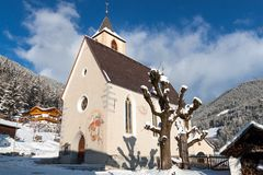 A wintertime view of a small church with a tall steeple Stock Photos