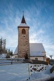 A wintertime view of a small church with a tall steeple Royalty Free Stock Photography