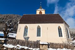 A wintertime view of a small church with a tall steeple Stock Photography