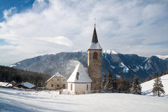 A wintertime view of a small church with a tall steeple Stock Image