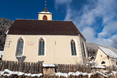 A wintertime view of a small church with a tall steeple Royalty Free Stock Image