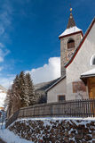 A wintertime view of a small church with a tall steeple Royalty Free Stock Photos