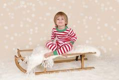 Winterurlaube: Lachendes glückliches Kind im Weihnachtspyjama-Schlitten Lizenzfreies Stockbild
