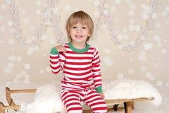 Winterurlaube: Lachendes glückliches Kind im Weihnachtspyjama-Schlitten Lizenzfreies Stockfoto