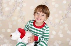 Winterurlaube: Lachendes glückliches Kind im Weihnachtspyjama-Schlitten Lizenzfreie Stockfotos