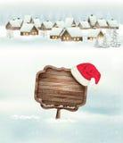 Winterurlaubweihnachtshintergrund mit einem Dorf Stockfoto