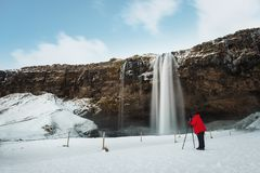 Winterwasserfalllandschaft, Fotograf in der roten Jacke, die Foto mit Kamerastativ an Seljalandsfoss-Wasserfall in Island macht lizenzfreies stockfoto