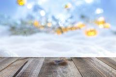 Winterweihnachtshintergrund mit abstrakten Lichtern des Holztischs und der Unschärfe Lizenzfreies Stockfoto