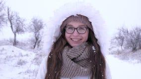 Winterwetter, freudig erregt Frau in die Gläser, die unter fallendem Schnee im Freilicht stehen stock footage
