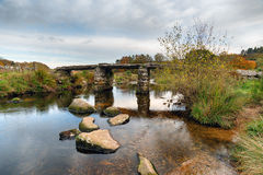 Wintery Day on Dartmoor. An old clapper bridge over the East Dart River at Postbridge on Dartmoor in Devon Stock Image