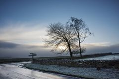 Wintery English sun on road to Hadrian`s Wall. Wintry sun shining through clouds on a frosty English road stock photos