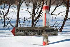 Wintery signpost in Sweden. Snow-covered signpost at snowmobile track in northern Sweden Royalty Free Stock Photo