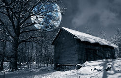 Wintery snow scenery with surreal full-moon. Old antique barn, 16th century surrounded by snow and frost, winter scenery with full moon, sweden Royalty Free Stock Photo