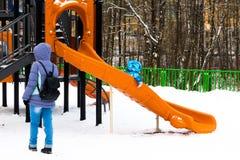 Winterzeit Aufpassendes Kleinkind der Mutter, welches das Dia auf dem Winkel des Leistungshebels schiebt lizenzfreies stockbild