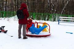 Winterzeit Aufpassendes Kleinkind der Mutter, welches das Dia auf dem Winkel des Leistungshebels schiebt lizenzfreie stockfotografie