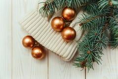 Winterzusammensetzung mit Tannenzweigen und goldenen Bällen auf der weißen Strickmütze Lizenzfreies Stockfoto