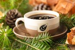 Winterzusammensetzung Tasse Kaffee, Kiefernniederlassungen auf Holztisch Stockbild