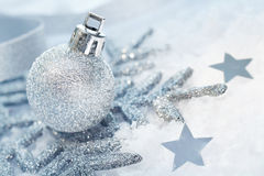 Wintry Christmas decorations. Atmospheric background of wintry silver Christmas decorations and stars in fresh snow Royalty Free Stock Photos