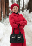 Wintry elegant mature lady. Mature woman in wintry clothes walking on the sidewalk Stock Photo