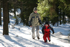 Wintry Fun. 2 young children frolick in the snowy forest, enjoying a nice winter morning outdoors stock image