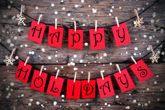 Wintry Happy Holiday Tags. Red Tags with Happy Holidays on it Hanging on a Line on Wood with Snow, Christmas or Winter Holiday Greetings royalty free stock photo