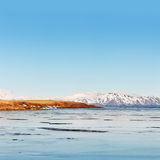 Wintry Iceland, frozen lake at fjord background Stock Image