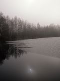 Wintry lake in countryside. Scenic view of lake in snowy countryside with Birch wood in background at twilight Royalty Free Stock Images