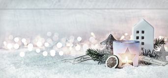 Wintry Merry Christmas festive panorama banner. With a decorative arrangement of pine cones and branches with a burning candle and cottage in fresh white snow Stock Image
