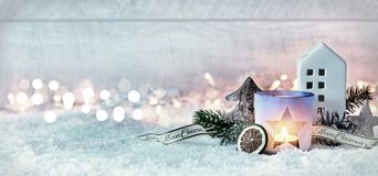 Wintry Merry Christmas festive panorama banner. With a decorative arrangement of pine cones and branches with a burning candle and cottage in fresh white snow Royalty Free Stock Photography