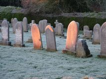Wintry Morning Graveyard. Wintry sun on headstones in graveyard royalty free stock photography