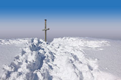 Wintry mountain trail and summit cross, blue sky Royalty Free Stock Photos