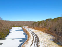 Wintry road running along the frozen river. A road touched by snow is running along the Blackwater river in West Virginia Royalty Free Stock Photo