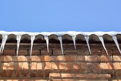 Wintry roof of the house with icicles on blue sky background.  royalty free stock photo