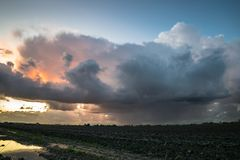 A wintry shower moves over the wide open dutch landscape in the western part of the country at sunset stock photos
