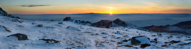 Wintry sunset panoramic background in mountain. Colorful panoramic scenery in snowy mountain Stock Images