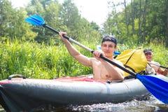 Wiosłować w kajaku przy weekendem Szczęśliwi faceci paddling podczas rzecznego flisactwa _ obraz stock