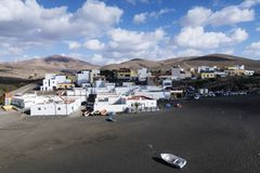 Wioska Ajuy na Fuerteventura z ciemną piasek plażą przeciw pasmu górskiemu i stronniczo chmurniejącemu niebieskiemu niebu Obrazy Royalty Free