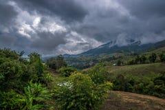 Wioska w wzgórzu lasowa góra z chmurnym niebem behind Zdjęcia Royalty Free