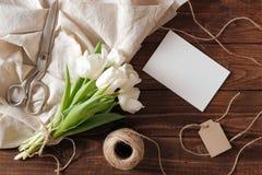 Wiosna bukiet biały tulipan kwitnie, pusta papierowa karta, nożyce, dratwa na nieociosanym drewnianym biurku Kobieta dnia skład n obrazy royalty free